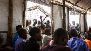 Oppilaita luokassa ja muita nuoria kurkkimassa ikkunan takaa.