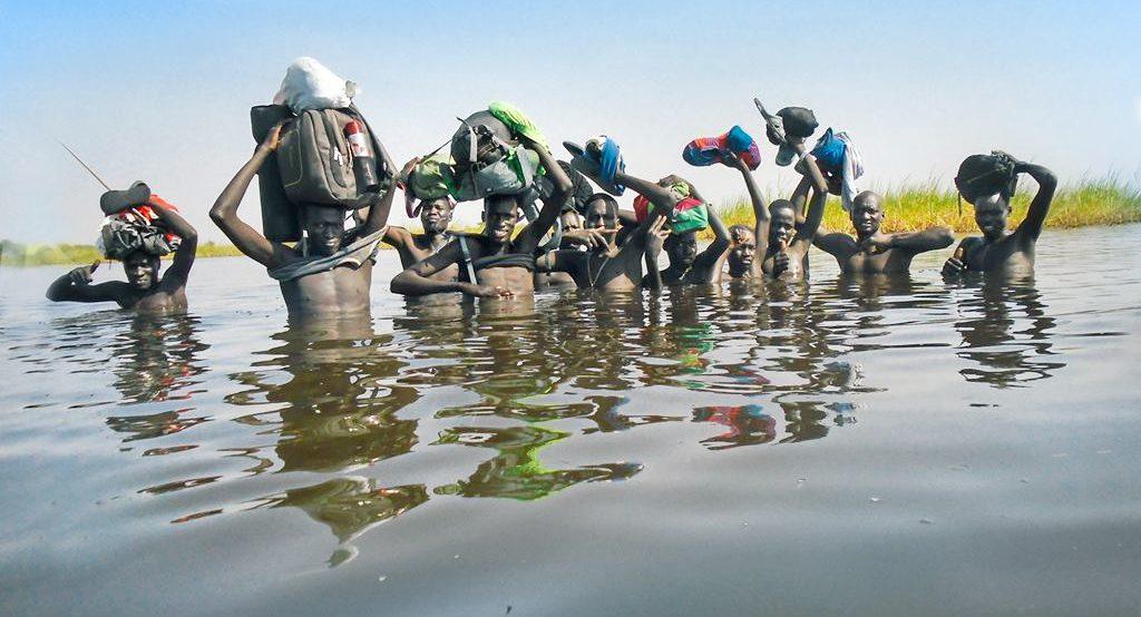KUA:n henkilöstö kantaa työreppunsa pään päällä Etelä-Sudanissa jokea ylitettäessä