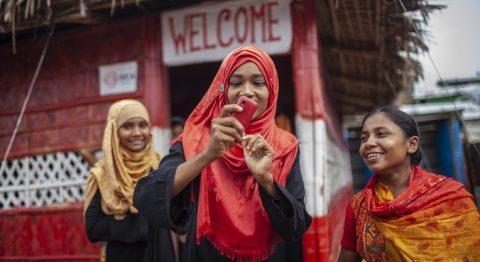 Kolme naista, jotka katsovat yhden kädessä olevaa kännykkää.