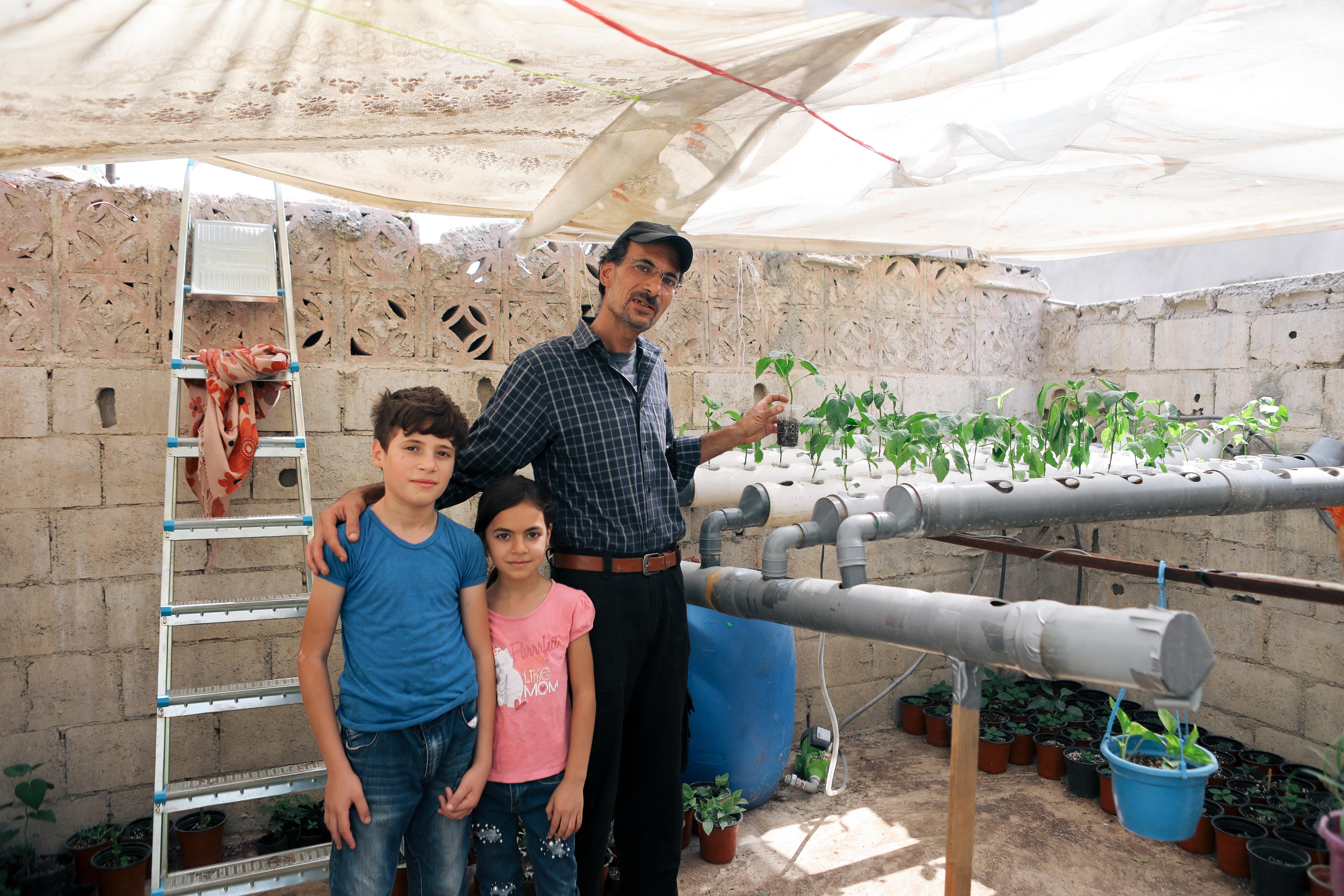 Ibrahim Milhem esittelee vesiviljelmän prototyyppiä.