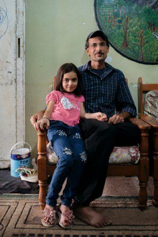 Ibrahim ja tytär layal istuvat nojatuolissa perheen olohuoneessa, taustalla näkyy Ibrahimin maalaama, puuaiheinen taulu.