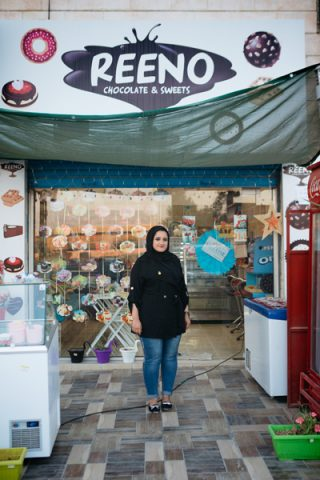 Ranaa stands in front of her shop.