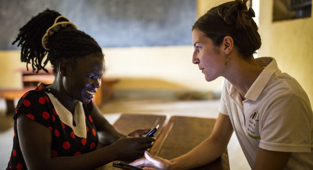 Opettaja Maurine Anguezaru ja KUA:n vapaaehtoinen Roosa Laine istuvat luokkahuoneessa.
