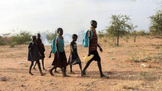 Kuusi eri-ikäistä kenialaista koululaista kävelee kuivuneella maalla aurinkoisena päivänä