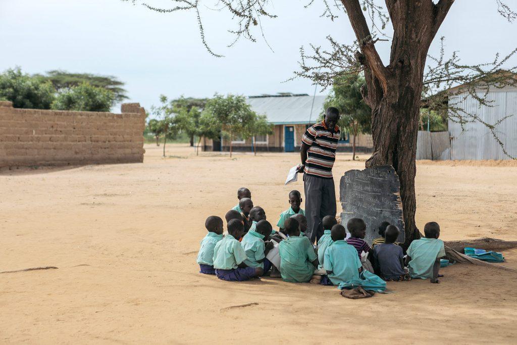 Oppilaat kerääntyneet opettajan ympärille puun alle. Liitutaulu puun runkoa vasten.