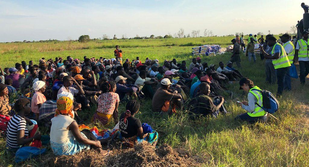 Kyläläiset istuvat heinikossa odottamassa omaa vuoroaan kuitata perheen ruokapaketti.