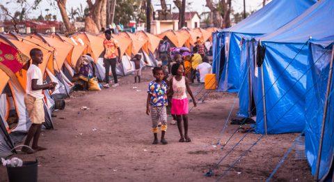 Kaksi lasta kulkee telttojen välissä.
