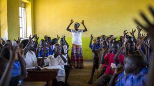 Opettaja on ohjannut pieniä koululaisia nostamaan kätensä ilmaan.