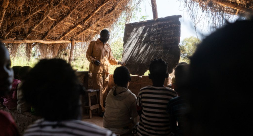 Bitobang Audre kirjoittaa liitutaululle ja oppilaat kuuntelevat.