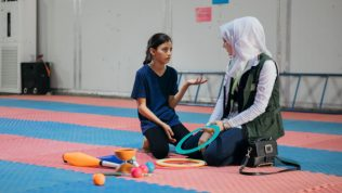 Nainen ja tyttö urheilusalin lattialla sirkustarvikkeiden kanssa.