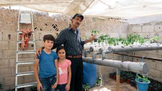 Ibrahim Milhem, hänen tyttärensä Layal Milhem ja hänen poikansa Forat kasvihuoneessa.