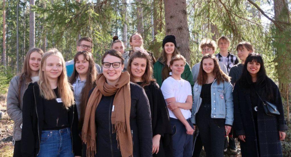 Joukko iloisia nuoria metsässä.