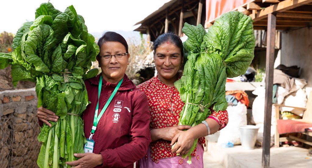 Naiset poseeraavat kylän raitilla isot sinapinlehtiniput olalla.