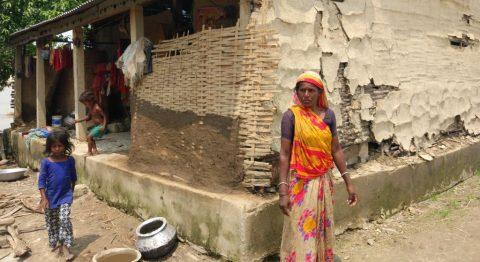 Debri Mukhiya tulvissa vahingoittuneen talonsa edessä Saptakoshissa.