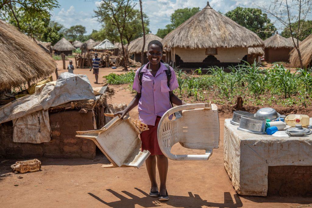 Iloinen nuori kantaa kahta muovituolia käsissään ja reppua selässään olkikattoisten majojen keskellä.