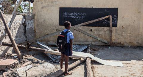 Mosambikilainen koululainen koulun raunioiden keskellä.