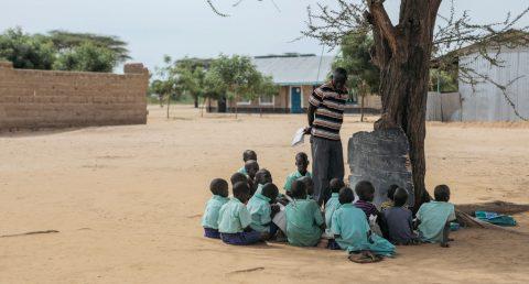 Pienet oppilaat ovat kerääntyneet piiriin, kun opettaja pitää tuntia liitutaulu puuta vasten hiekkakentällä.