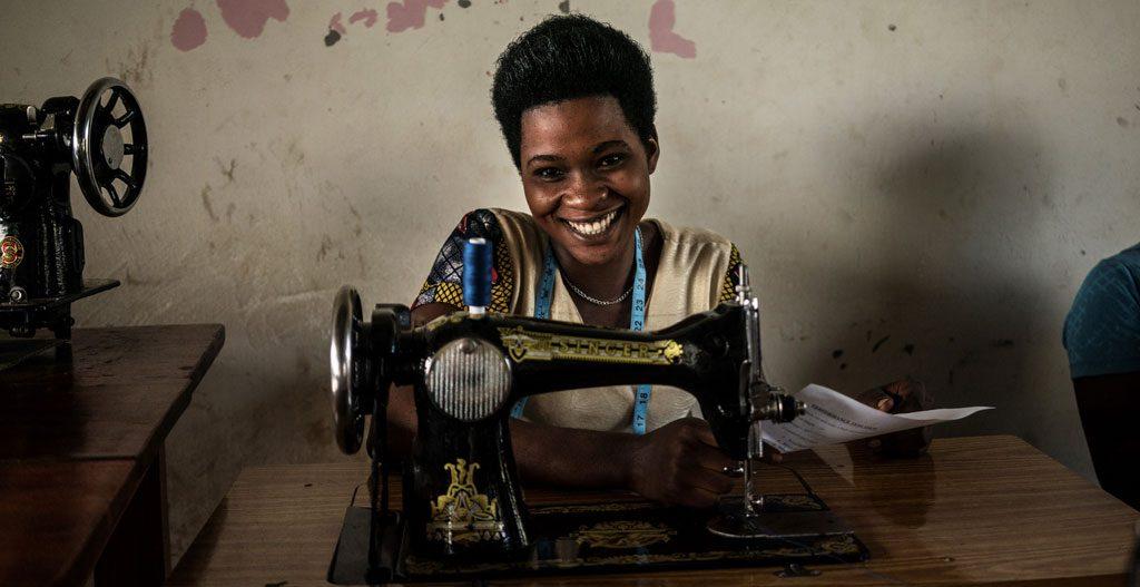 Nainen hymyilee iloisesti ompelukoneen takaa.