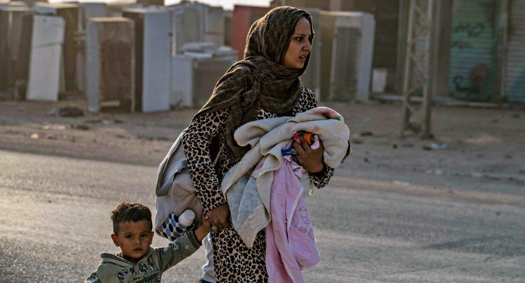 Syyrialainen äiti pakenee lapsensa kanssa Turkin pommituksia Koillis-Syyriassa Ras-al-Ain kaupungissa.