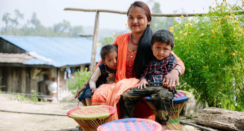 Nainen kaksi lasta kainaloissaan.
