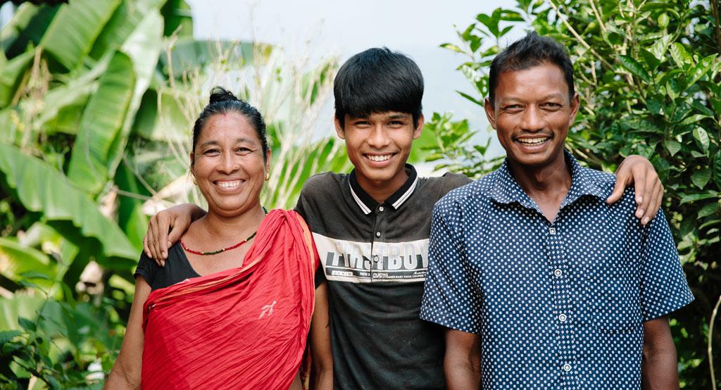 Äiti, lapsi ja isä hymyilevät iloisesti viljelysten keskeltä.