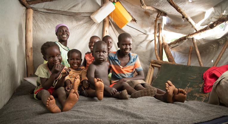 Agnes hymyilee yhdessä kuuden pienen lapsensa kanssa pressukangasteltassa.