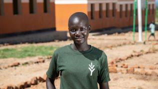 Sharon seisoo koulunsa edustalla Bidibidin pakolaisasutusalueella Ugandassa.