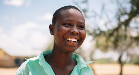 Silvia hymyilee aurinkoisesti koulupuku päällään Pohjois-Keniassa.