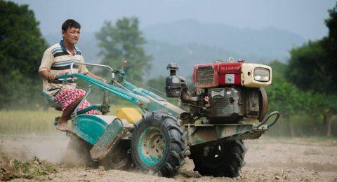 Nepalilainen Khincha Lal Pahari ajaa traktorilla pellolla.