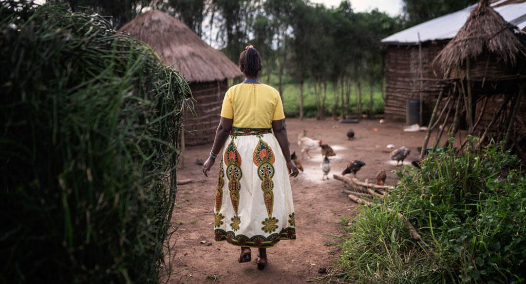 Kauniiseen hameeseen pukeutunut nainen kävelee pihapiiriin, jossa maata nokkii monta kanaa.