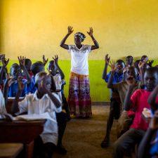 Koululuokka Ugandassa. Opettaja seisoo keskellä luokkahuonetta kädet nostettuna ilmaan. Myös pulpeteissa istuvat oppilaat ovat nostaneet kätensä ylös.