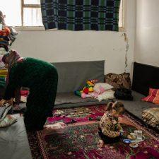 Mariam al-Issa järjestelee tyynyjä ja peittoja pakolaiskeskuksen huoneen nurkkaan päivän ajaksi. Pieni tyttärentytär istuu lattialla. Huoneen reunoja kiertävät lattialle asetetut patjat.