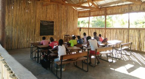 Oppilaita istuu pulpeteissa uudessa koululuokassa.