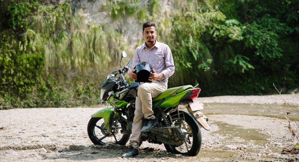 Mies istuu moottoripyörän päällä.