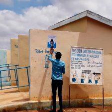 Mies kiinnittää julistetta, jossa opatetaan niistämään oikein, koulun ulkowc:n seinään Somaliassa. Vessoissa invarampit.