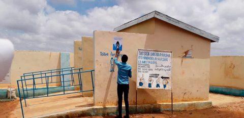 En man hänger upp affischer på väggen.