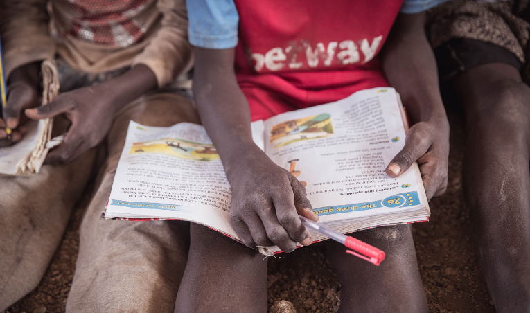 A kenyan student with a book on his lap.