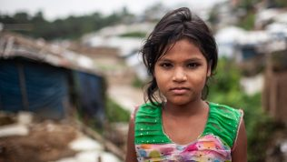 Tyttö seisoo teltta-asutuksen edessä pakolaisleirillä.