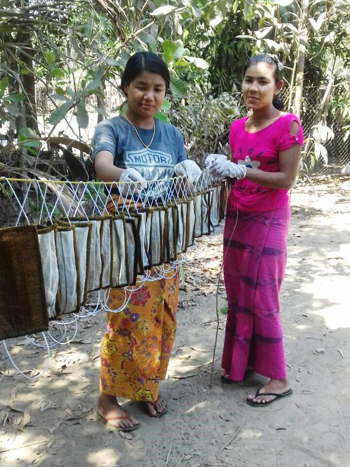 Myanmarilaisia ompelijoita valmiiden hengityssuojaimien kanssa.
