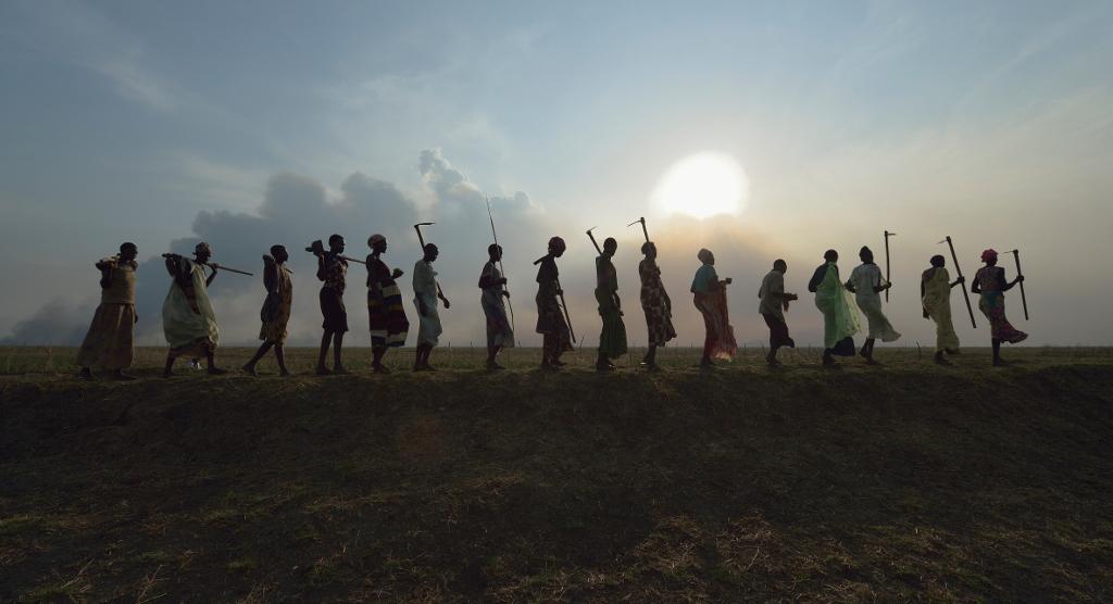 Etelä-sudanilaisia maanviljelijöitä menossa kotiin