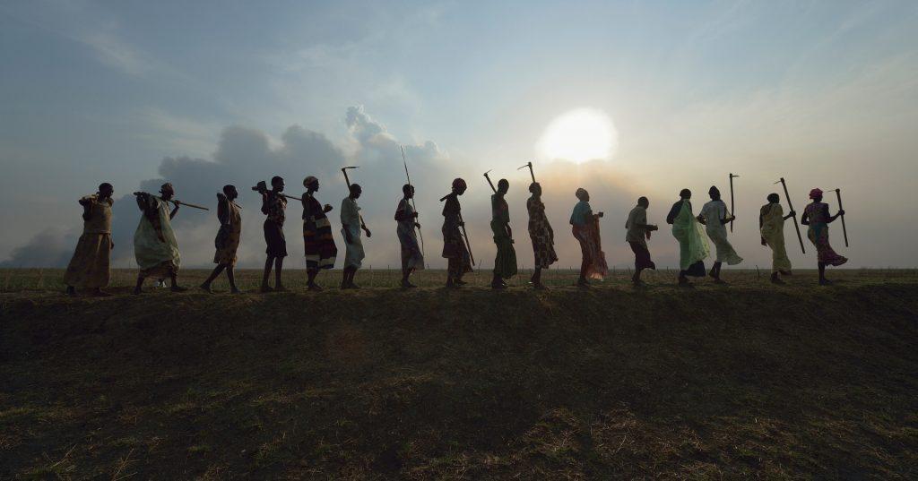 Etelä-sudanilaisia maanviljelijöitä menossa kotiin.