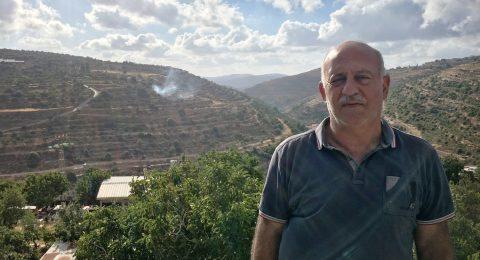 Palestiinalainen mies seisoo, taustalla vihreitä kukkuloita.