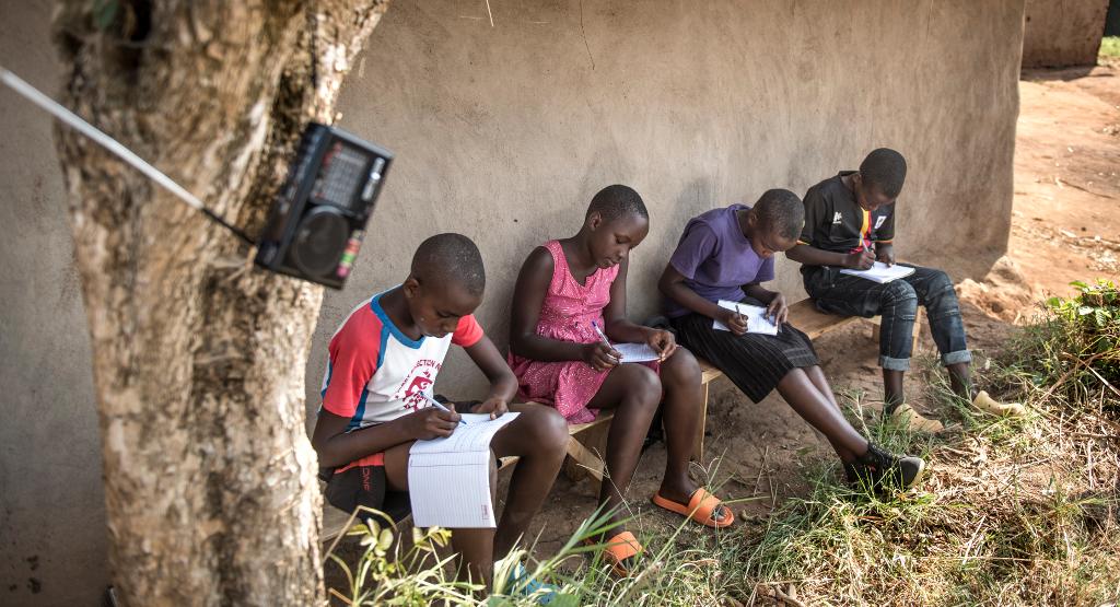 Ugandalaisia koululaisia Rwamwanjan pakolaisalueella istumassa koulun edessä