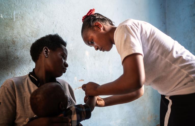 Sairaanhoitaja Anitah Owaruhanga hoitaa potilasta klinikallaan.
