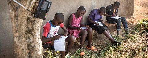 Ugandalaisia koululaisia kuuntelemassa etäopetusta radiosta