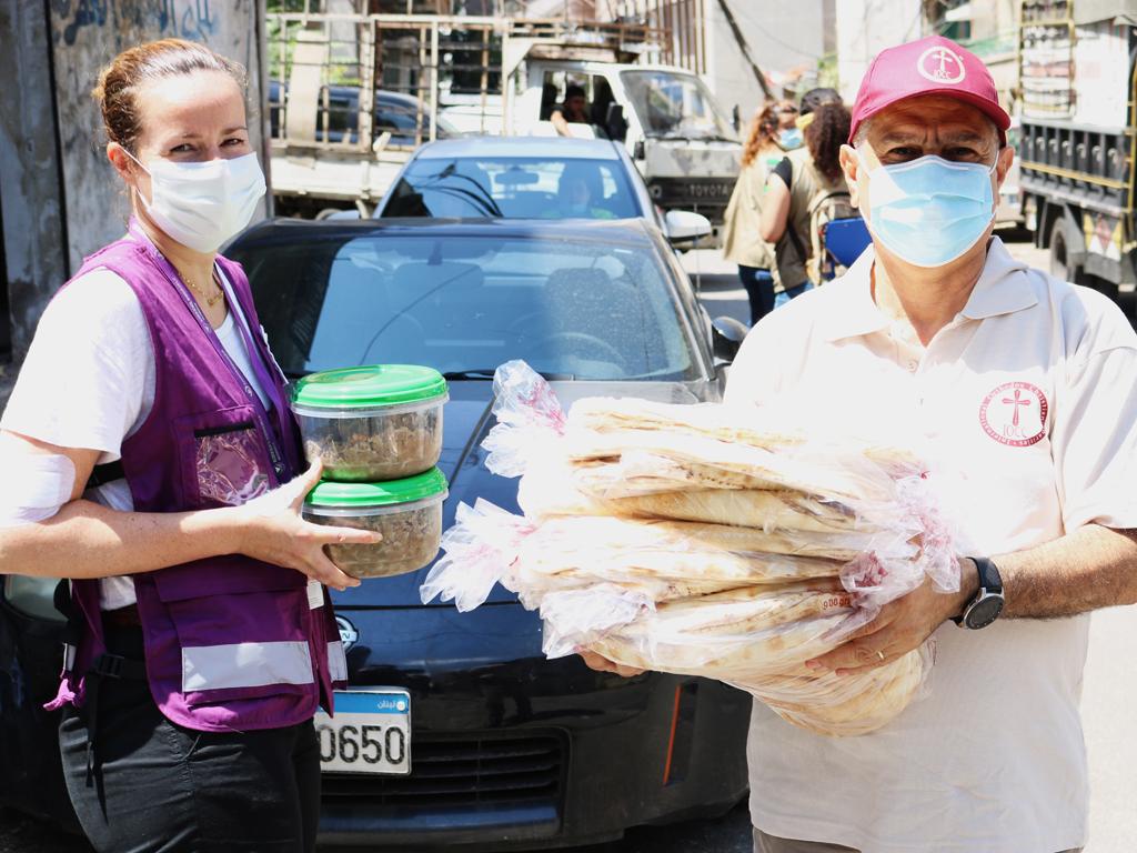 Kaksi avustustyöntekijää kasvomaskeissa pitele ruoka-astioita ja leipäpusseja käsissä kadulla.