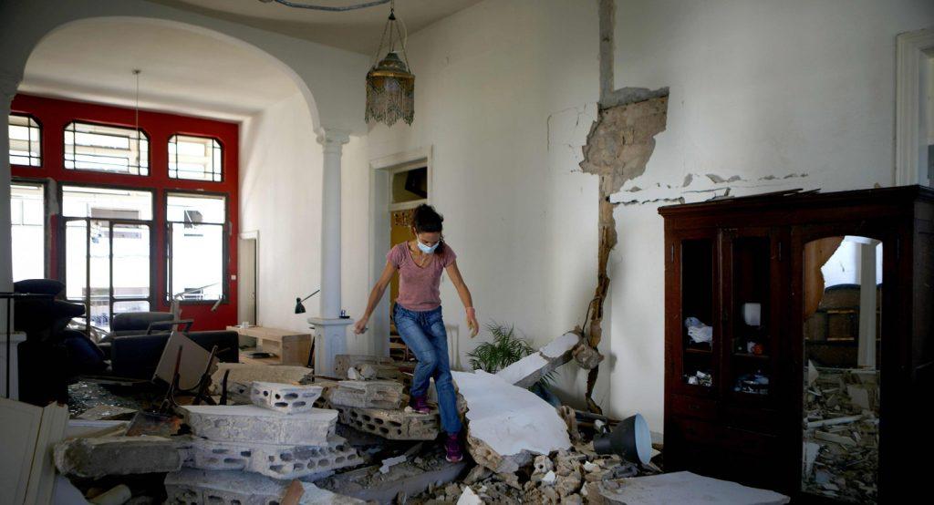 En ung kvinna klättrar över ruinerna i ett rum.