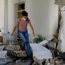 Nuori nainen kiipeää rakennusmurskan yli tuhoutuneessa huoneessa Beirutissa.