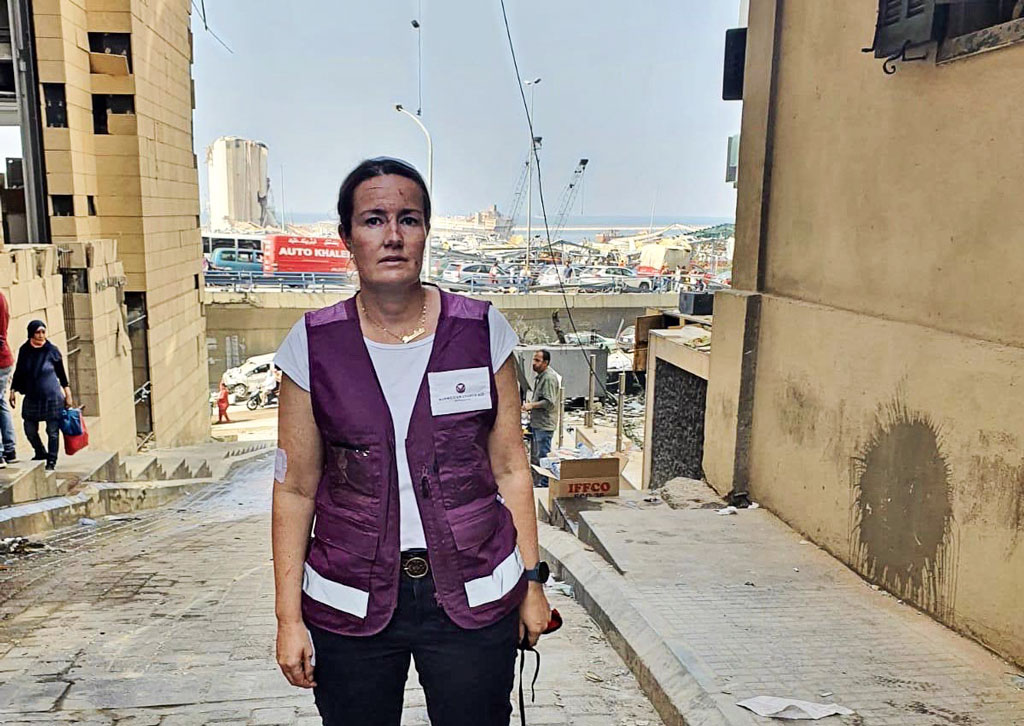Nainen seisoo vauriotuneen Beirutin sataman luona avustusjärjestön liivit päällä.