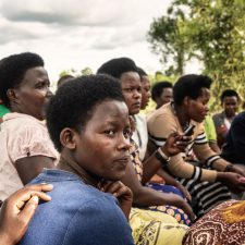 Parikymmentä naista istuu ulkona katselemassa ja kuuntelemassa